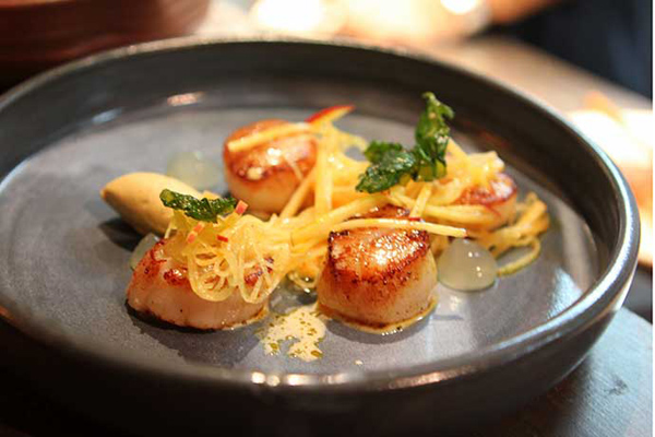 Seared scallops, foie gras, curry emulsion, apple, mooli. Image credit: Taste.