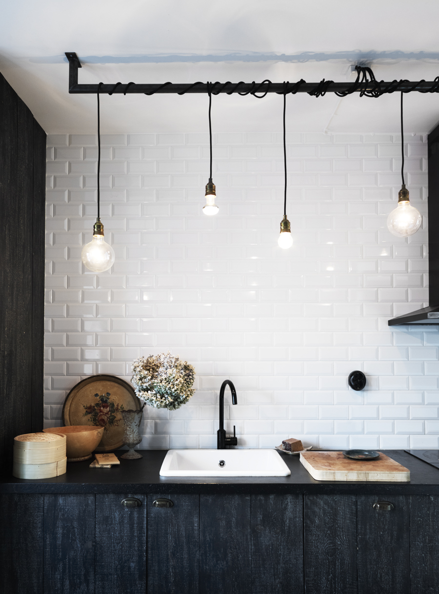 Stained black Ikea cabinets contrast with the white subway tile. Photograph by Anna Kern for Skona Hem.